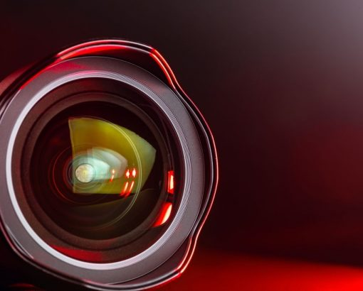 The camera lens with red light. Close-up of the camera lens on a black background with red illumination. Optics.