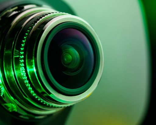 The camera lens and light green. Side view of the lens of camera on green background. Camera Lens close Up. Optics